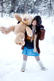 Happy woman in fur coat and ushanka with bear on white snow winter background Stock Photo