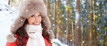 Happy woman in fur hat over winter forest royalty free stock photo