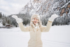 Happy woman in fur hat throwing up snow while standing outdoos. Magical mix of winter season and mountain landscape create the perfect mood. Happy young woman in Royalty Free Stock Photography