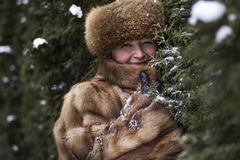 Happy woman in fur jacket among bushes. In winter Stock Photography