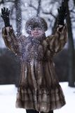 Happy woman in fur jacket among snow. In winter Stock Photo