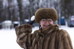 Happy woman in fur jacket among snow Stock Photo