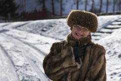 Happy woman in fur jacket among snow. In winter Stock Photography