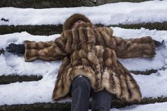 Happy woman in fur jacket among snow Stock Photography