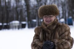 Happy woman in fur jacket among snow. In winter Royalty Free Stock Photo