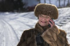 Happy woman in fur among snow. In winter Royalty Free Stock Photos