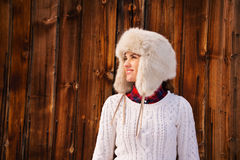 Happy woman in furry hat near rustic wood wall looking aside Stock Photography