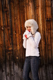 Happy woman in furry hat with red cup near rustic wood wall Royalty Free Stock Images