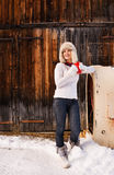 Happy woman in furry hat with red cup near rustic wood wall Stock Photography