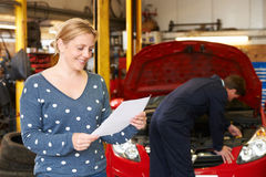 Happy Woman With Garage Repair Bill Royalty Free Stock Photography