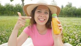Happy woman in the garden is going to drink orange juice stock video