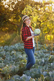 Happy woman gardener with cabbage. Happy young woman gardener with cabbage in garden with sunshine. Young farmer harvesting cabbage. Gardening, agriculture Stock Photo