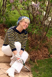 Happy woman gardening. Older caucasian woman in gardening gloves smiling Stock Photography