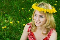 Happy woman in a garland of dandelions. Happy beautiful blond hair woman in garland sitting on the grass among dandelions Stock Images