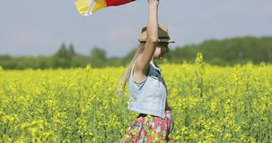 A happy woman with a German flag is walking on a yellow rapeseed field in summer. Flag of Germany fluttering in the wind stock video footage