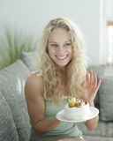 Happy woman gesturing while holding cake in house Stock Photography