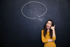 Happy woman gesturing talking on phone over blackboard background Royalty Free Stock Images