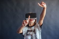 Happy woman gets experience of using VR-glasses virtual reality headset. Stock Photography