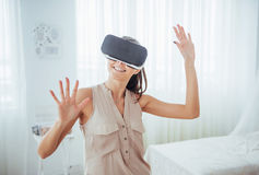 Happy woman gets experience of using VR-glasses virtual reality headset in a bright studio Royalty Free Stock Image