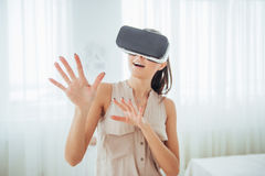 Happy woman gets experience of using VR-glasses virtual reality headset in a bright studio Stock Photos
