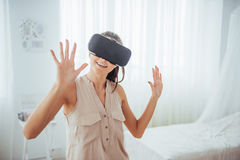 Happy woman gets experience of using VR-glasses virtual reality headset in a bright studio Royalty Free Stock Photo