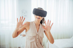 Happy woman gets experience of using VR-glasses virtual reality headset in a bright studio Stock Images