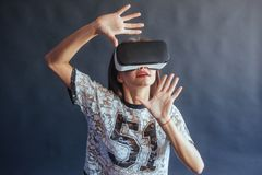 Happy woman gets experience of using VR-glasses virtual reality headset. Royalty Free Stock Images