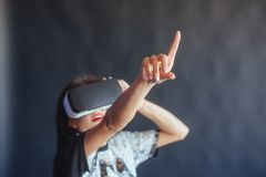 Happy woman gets experience of using VR-glasses virtual reality headset. Royalty Free Stock Photography
