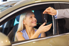 Happy woman getting car key in auto show or salon. Auto business, car sale, consumerism and people concept - happy woman taking car key from dealer in auto show Stock Photos