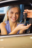 Happy woman getting car key in auto show or salon Royalty Free Stock Images