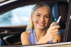 Happy woman getting car key in auto show or salon Royalty Free Stock Photo
