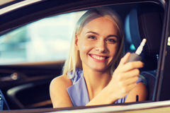 Happy woman getting car key in auto show or salon Stock Images