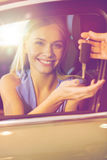 Happy woman getting car key in auto show or salon Royalty Free Stock Photography