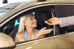 Happy woman getting car key in auto show or salon Royalty Free Stock Image