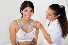 Happy woman getting electrodes therapy Stock Photo