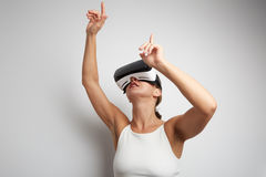 Happy woman getting experience using VR headset glasses of virtual reality at home much gesticulating hands. Royalty Free Stock Photography