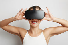 Happy woman getting experience using VR headset glasses of virtual reality at home much gesticulating hands. Royalty Free Stock Images