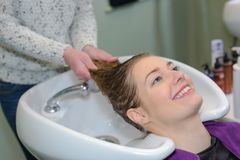 Happy woman getting hairwash by hairdresser. Happy woman is getting a hairwash by a hairdresser Stock Images