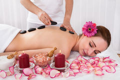 Happy woman getting hot stone therapy Stock Photography