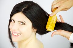 Happy woman getting long hair combed and new hairdo Royalty Free Stock Photography