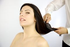 Happy woman getting long hair styled by professional coiffeur Stock Images
