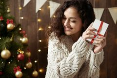 Happy woman with gift box in christmas decoration. Dark wooden interior with lights. Romantic evening and love concept. New year h. Oliday Stock Images