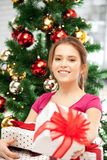 Happy woman with gift box and christmas tree Stock Photography