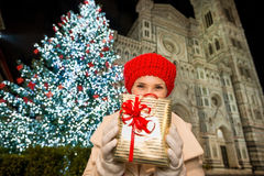 Happy woman with gift box near Christmas tree in Florence, Italy. Happy young woman in white coat hiding behind gift box in front of Christmas tree near Duomo in royalty free stock photography