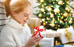 Happy woman with gift at morning near Christmas tree Stock Photos
