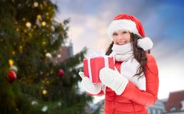 Happy woman with gift over christmas tree stock photos