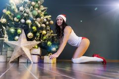 Happy woman with gift under christmas tree. Young beautiful girl in lingerie and Santa Claus cap puts a Christmas gift. royalty free stock photo
