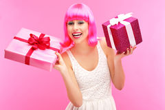 Happy woman with gifts. Woman wearing wig over pink background Stock Photo
