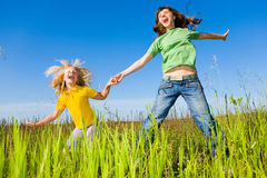 Happy woman and girl making exercises on field. Royalty Free Stock Photography