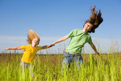 Happy woman and girl making exercises on field Stock Photos